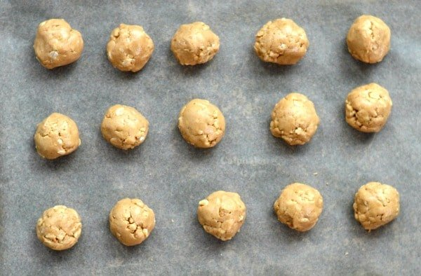 peanut butter balls rolled on parchment paper