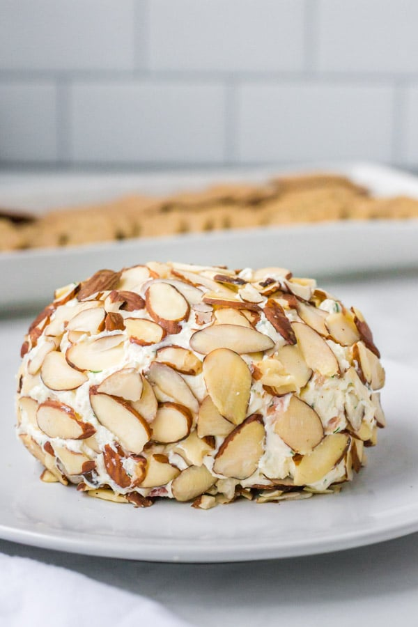 bacon dill cheese ball covered with almonds on a white plate