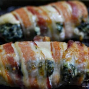 closeup of chicken breast stuffed with spinach and cream sheese mixture and then wrapped in bacon