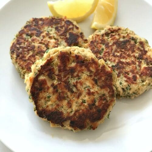 three tuna patties on a white plate with lemon wedges