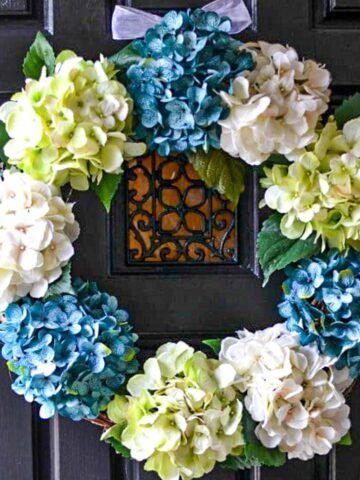 hydrangea wreath with blue, white and pale green flowers on a black door