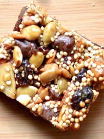 square energy bar with pumpkins seeds, raisins, quinoa, dates on a wood table