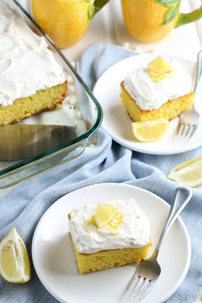 two slices of lemonade cake with lemon frosting on white plates with glass baking dish in the background
