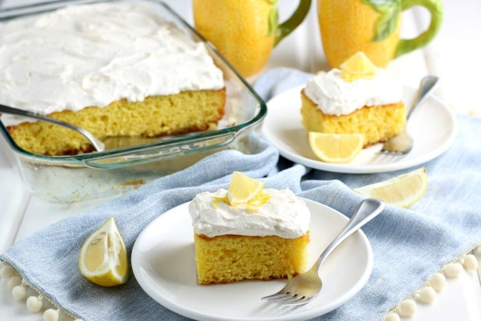 2 slices of lemonade cake with frosting on white plates with whole cake pan and 2 yellow mugs in background