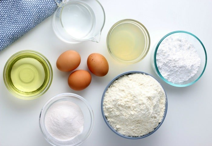 Bowls of ingredients for lemon cake on a table, eggs, flour, oil, sugar.