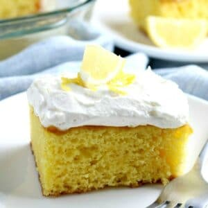 A piece of lemon cake with vanilla frosting on a plate