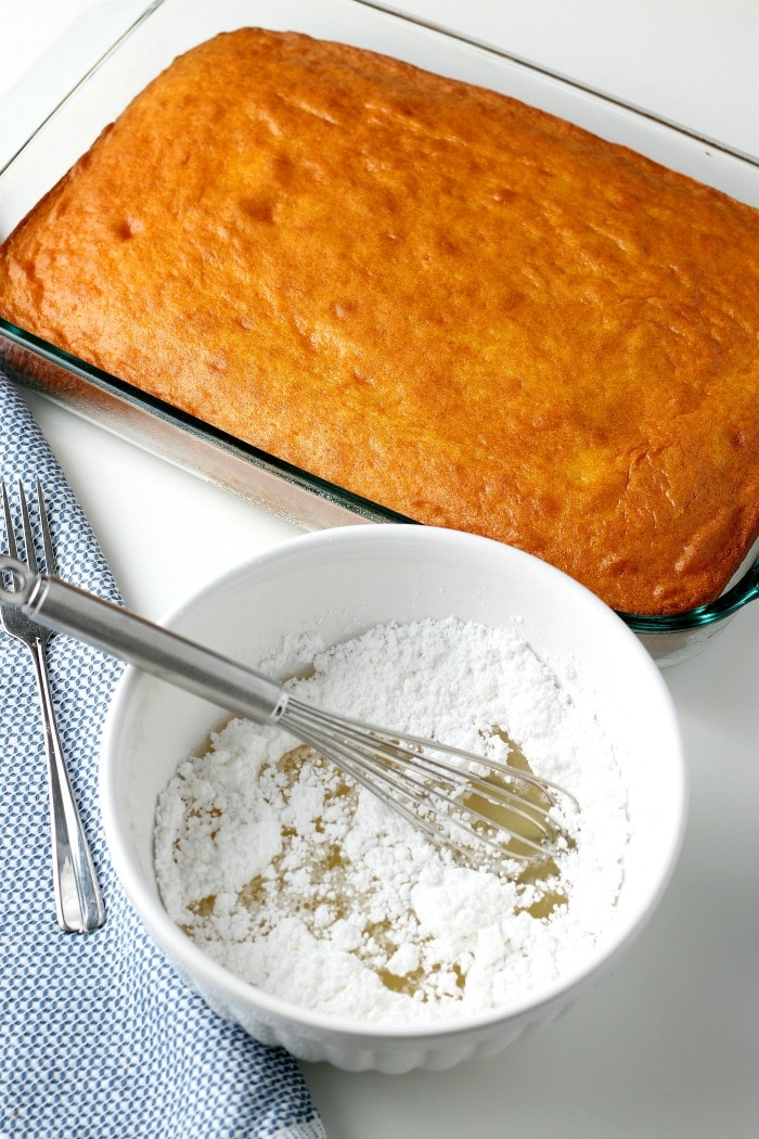 overhead picture cooked sheet cake with bowl of powdered sugar