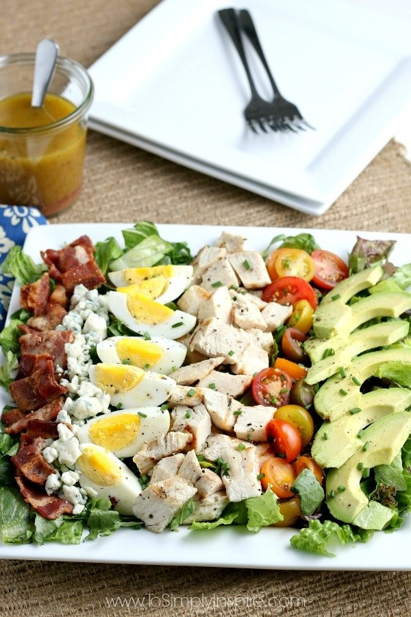 Layered Cobb Salad on a rectangle white plate with bacon, chicken, hard boiled eggs, tomatoes, avocado and blue cheese
