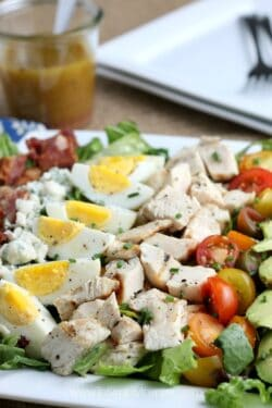 Closeup of ayered Cobb Salad on a rectangle white plate