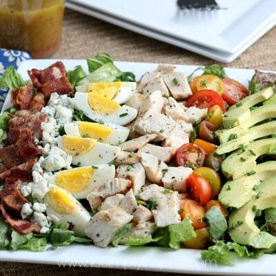 Cobb Salad layered with bacon, chicken, hard boiled eggs, tomatoes, avocado and blue cheese