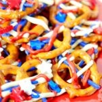 Patriotic Pretzels covered with red white and blue sprinkles on a red plate