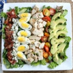 cobb salad with avocado, hard boiled eggs, chicken bacon and tomatoes lined in a row
