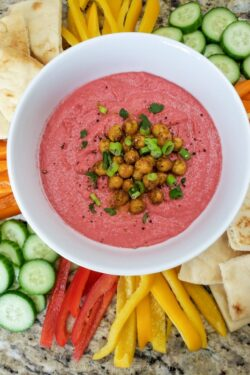 beet hummus in a white bowl surrounded by fresh vegetables