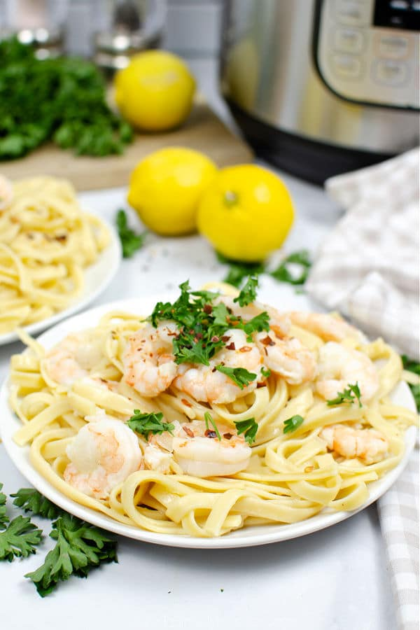 shrimp scampi over fettuccine noodles on a white plate with 2 lemons