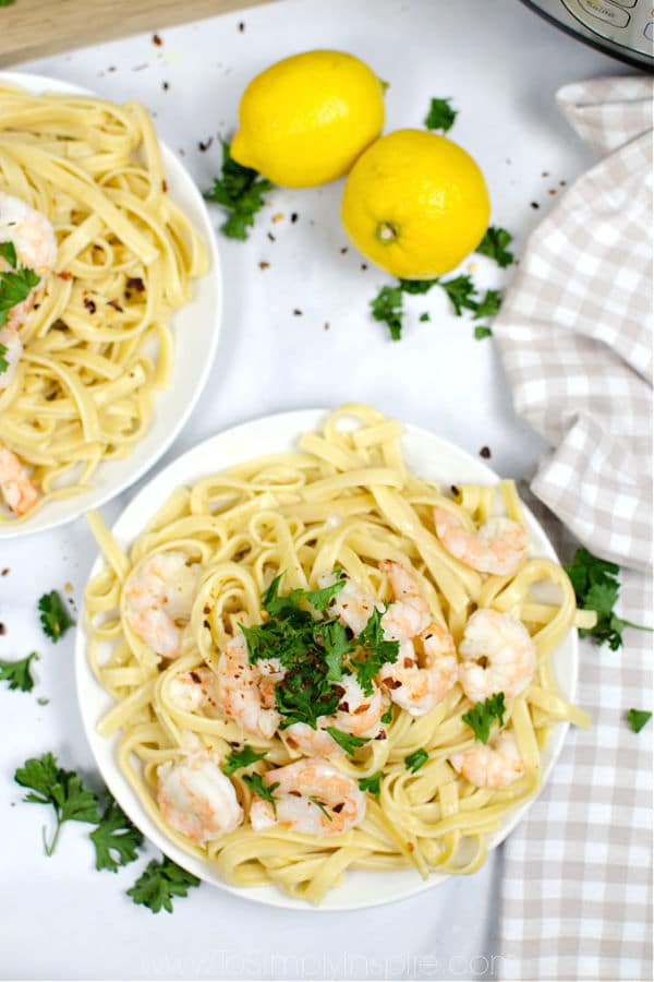 two white plates full of shrimp scampi over fettuccini noodles
