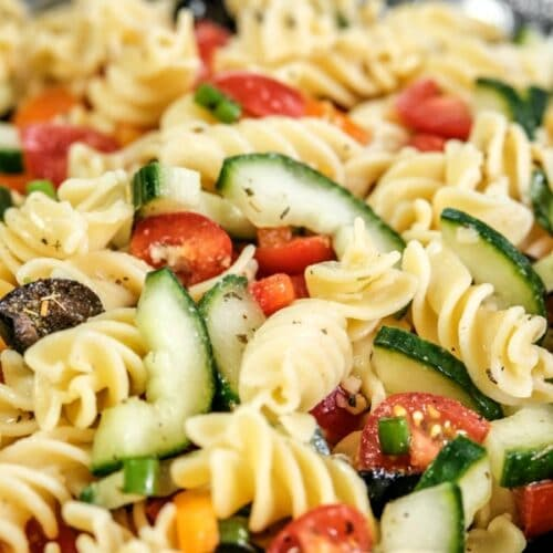 closeup of pasta salad with tomatoes, olives and cucumbers