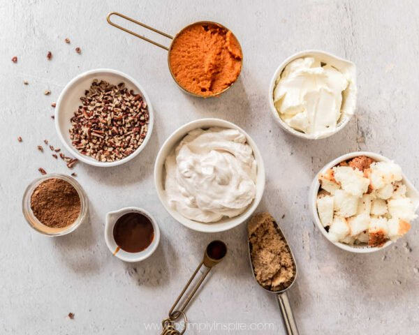 Several ingredients for pumpkin cheesecake trifles in measuring cups and bowls