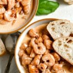 closeup of sweet potato gnocchi with shrimp in a white bowl with 2 slices of bread