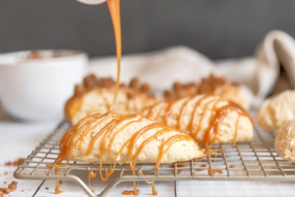 apple scones on a cooking rack being drizzled with caramel sauce
