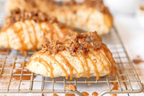 three apples scones on a metal cooling rack topped with cinnamon sugar crumb topping