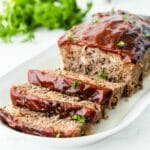 Meatloaf with 3 slices cut on a white plate with parsley in the background