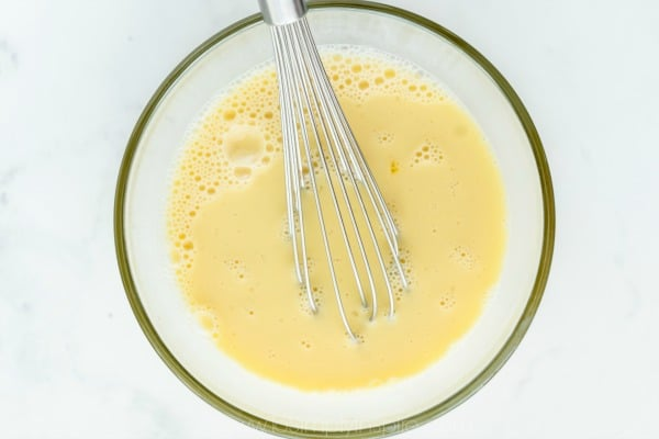 Eggs being whisked in a glass bowl