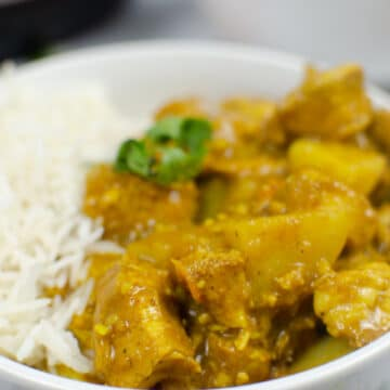 closeup of Chicken curry over rice in a white bowl
