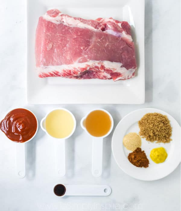uncooked pork shoulder and white measuring cups with ingredients
