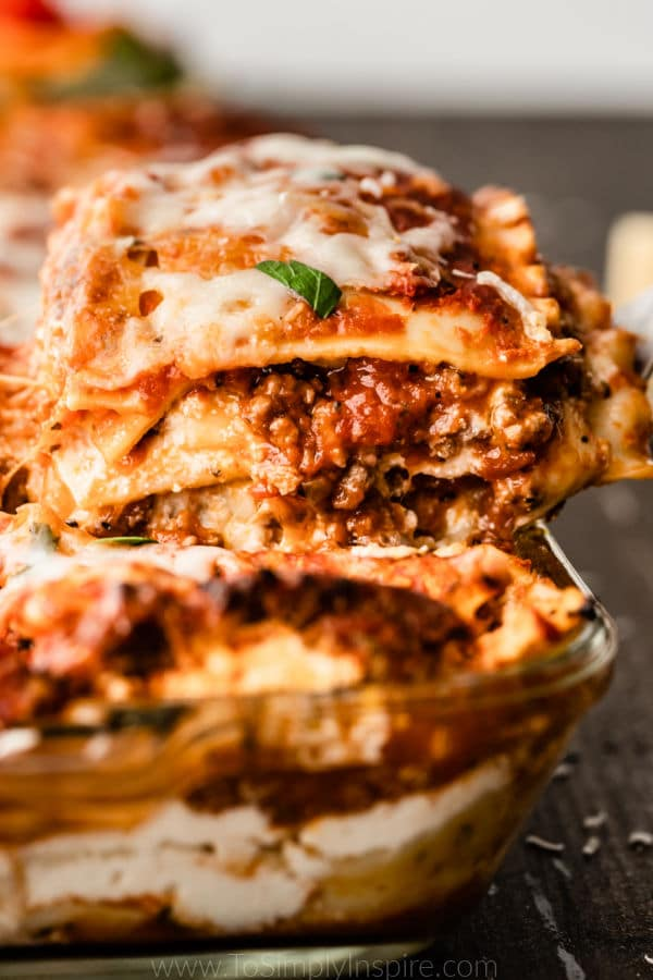 slice of lasagna being scooped out of baking dish