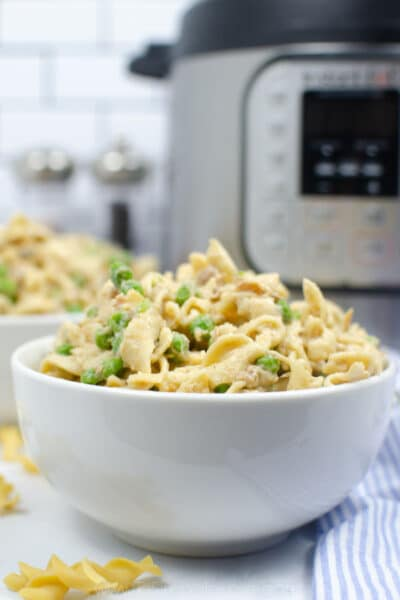 closeup of tuna casserole in a white bowl with instant pot in background