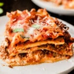 closeup of a slice of lasagna on a white plate