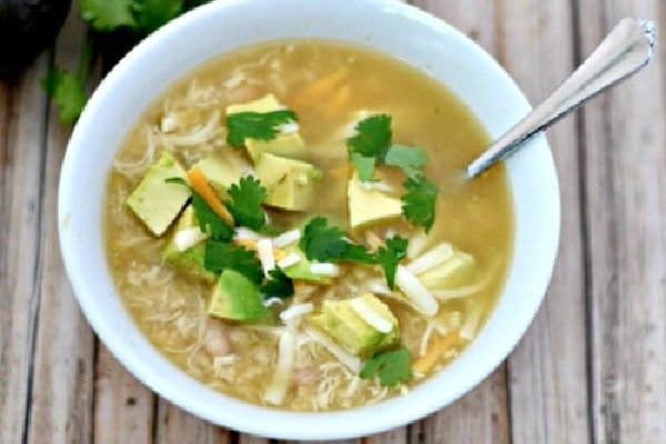 white chicken chili in a bowl with a spoon and topped with cilantro