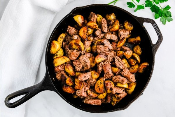 cast iron skillet with steak bites and potatoes