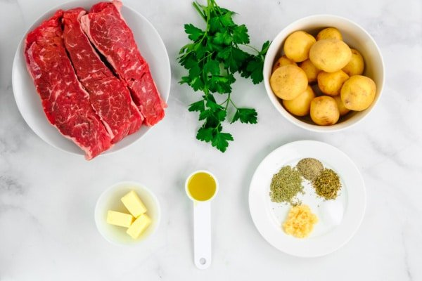 Uncooked steak on a plate, uncooked potatoes in a bowl, fresh parsley, and spices