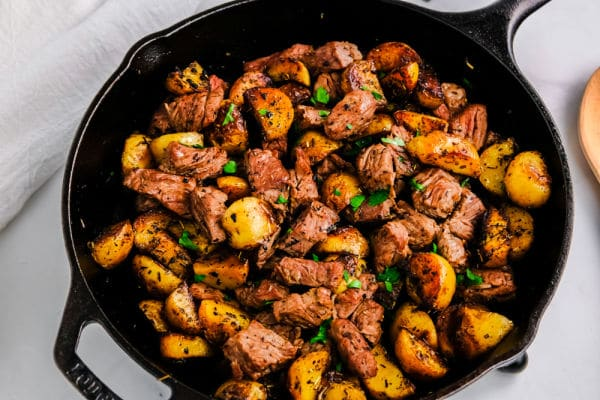 steak bites and potatoes in a cast iron pan