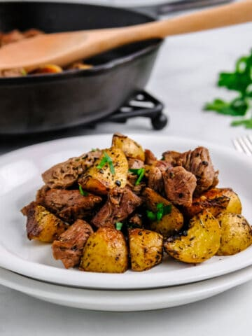 butter steak bites and potoes on a white plate with cast iron skillet in the background