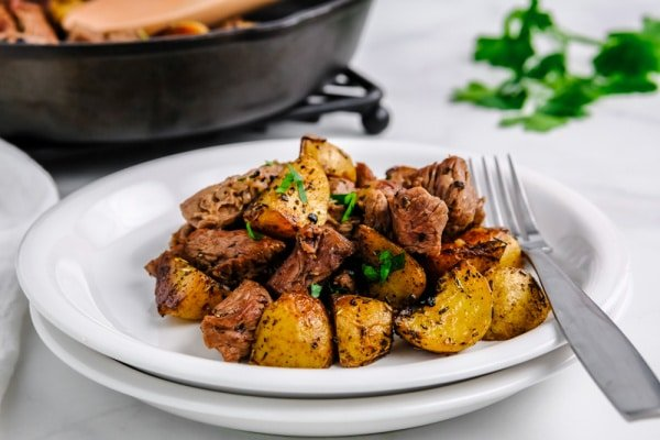 steak bites and potatoes on a white plate with a fork