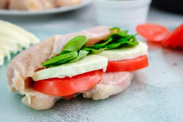 closeup of raw chicken breast stuffed with tomato slice, mozzarella and fresh basil leaves