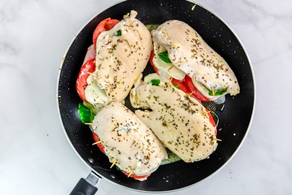 four chicken breasts cooking in a black skillet