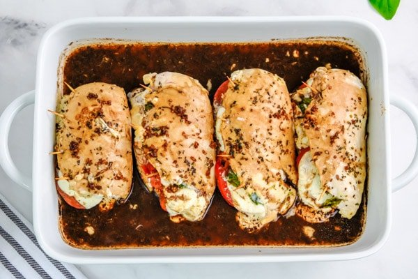 four chicken breasts covered with balsamic vinegar in a white casserole dish