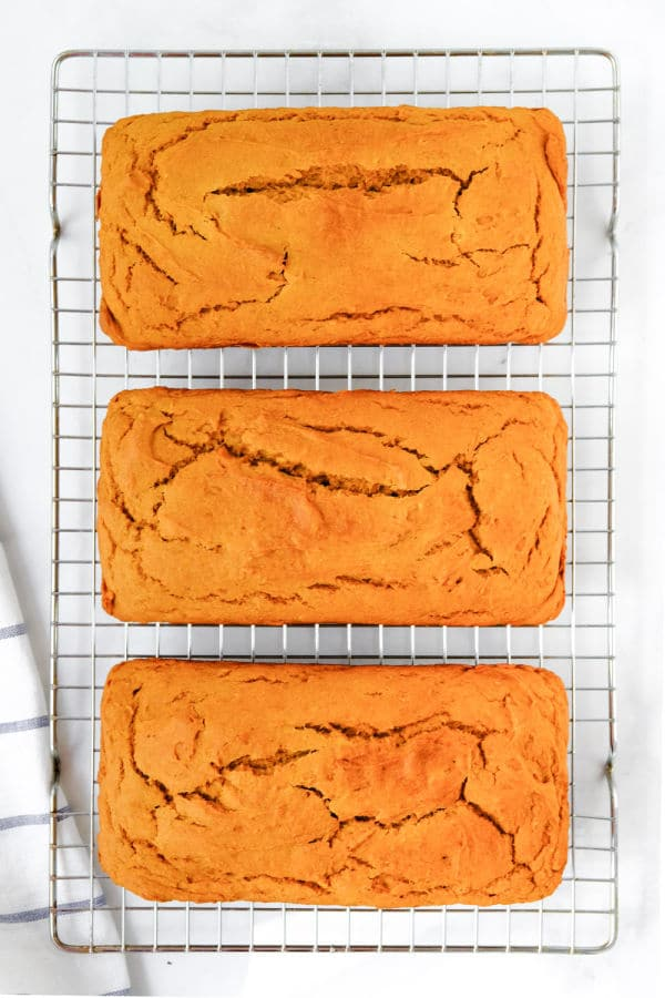 three loaves of sweet potato bread on a wire cooling rack