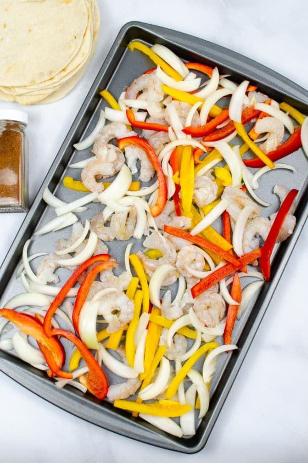 uncooked shrimp, sliced onions sliced red and yellow peppers on a baking sheet