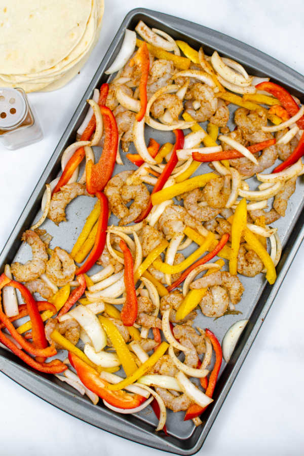 shrimp, sliced onions sliced red and yellow peppers on a baking sheet