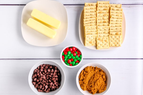 ingredients for Christmas crack and a table: saltine crackers, butter, brown sugar, chocolate chips