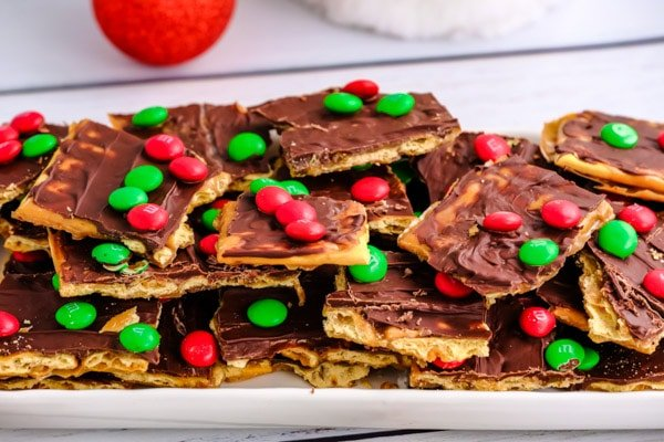 a white rectangle plate full of christmas crack saltine toffee