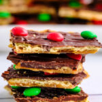 a stack of christmas crack toffee with a plateful in the background