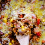closeup of cheesy Mexican casserole being scooped out of a slow cooker