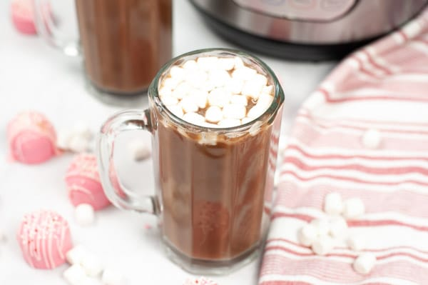 hot cocoa in a glass mug topped with mini marshmallows