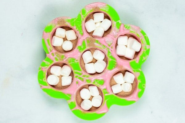 seven circle silicon molds filled with hot cocoa powder and marshmallows
