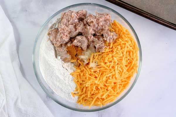 shredded cheese, sausage, and bisquick in a glass mixing bowl